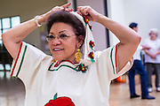 27 JUNE 2012 - GLENDALE, AZ:  MARGIE MAY, 65 years old, puts on her outfit before a dress rehearsal for the Senior Fiesta Dancers at the Glendale Adult Center, in Glendale, AZ, a suburb of Phoenix. Dancing as a part of workout regimen is not unusual, but the Senior Fiesta Dancers use Mexican style folklorico dances for their workouts. The Senior Fiesta Dancers have been performing together for 15 years. They get together every week for rehearsals and perform at nursing homes and retirement centers in the Phoenix area once a month or so. Their energetic Mexican folklorico dances keep them limber and provide a cardio workout.   PHOTO BY JACK KURTZ