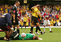 Photo: Frances Leader.<br /> Watford v Burnley. Coca Cola Championship.<br /> 20/08/2005.<br /> <br /> Burnley's Goal Keeper Brian Jensen lies on the floor injured while Watford's Matthew Spring celebrates the third goal of the game for Watford and referee Matt Messias who allowed play to continue, walks past.