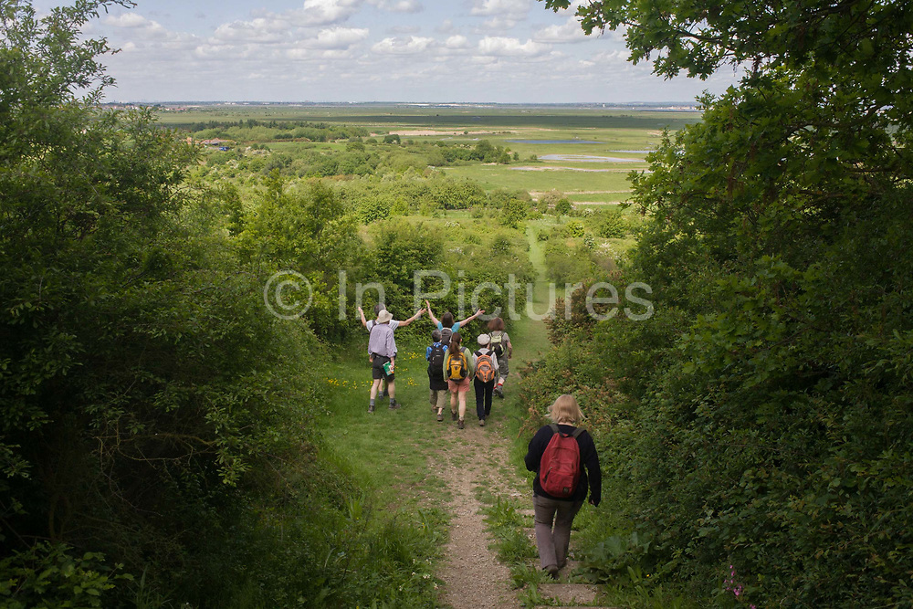 A group of country ramblers look across Northwood Hill's landscape below, an wildlife area near Halstow on the Kent Thames estuary marshes, potentially threatened by the future London airport. With the panoramic views beyond, the walkers stop to admire the landscape that could controversially become the site for London's estuary airport, built on reclaimed and marshland on the river Thames, east of the city. Current London mayor Boris Johnson is in faviour of this project to alleviate pressure from other airport hubs, regardless of wildlife (especially a nearby protected bird sanctuary).