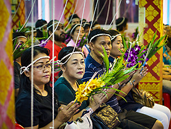 June 24, 2017 - Bang Kruai, Nonthaburi, Thailand - People pray during a ''resurrection'' or rebirthing ceremony at Wat Ta Kien (also spelled Wat Tahkian), a Buddhist temple in the suburbs of Bangkok. The strings around their heads are connected to a web of strings that is supposed to amplify the power of the prayers. People go to the temple to participate in a ''Resurrection Ceremony.'' Thai Buddhists believe that connecting people by strings around their heads, which are connected to a web of strings suspended from the ceiling, amplifies the power of the prayer. Groups of people meet and pray with the temple's Buddhist monks. Then they lie in coffins, the monks pull a pink sheet over them, symbolizing their ritualistic death. The sheet is then pulled back, and people sit up in the coffin, symbolizing their ritualist rebirth. The ceremony is supposed to expunge bad karma and bad luck from a person's life and also get people used to the idea of the inevitability of death. Most times, one person lays in one coffin, but there is family sized coffin that can accommodate up to six people. The temple has been doing the resurrection ceremonies for about nine years. (Credit Image: © Jack Kurtz via ZUMA Wire)