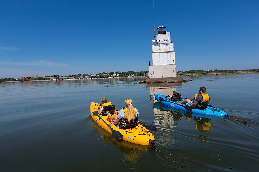 The Ludtke family peddle kayaks past the lighthouse in Manitowoc, Wisconsin.  Photo by Mike Roemer