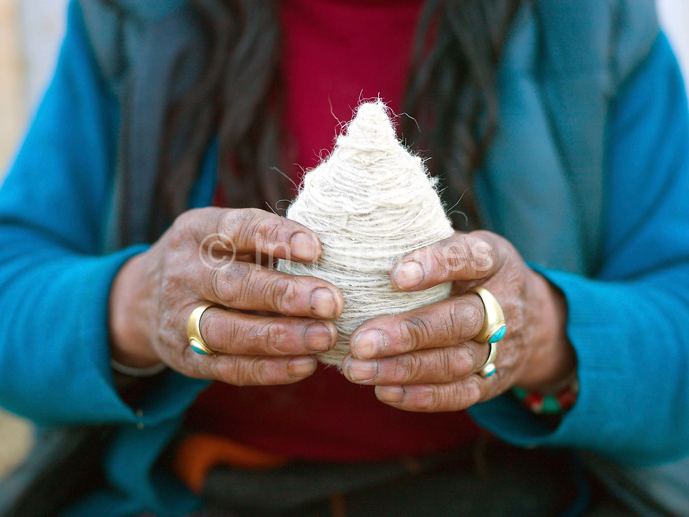 A Layap woman from Laya holds a ball of sheep wool which was spun using a drop spindle called a Yoekpa, Punakha, Western Bhutan. The Layap are inhabitants of the northernmost region of Bhutan. Their clothes are woven from yak hair and wool. They are a semi-nomadic tribe whose source of livelihood is dependent on yaks and sheep the products of which they barter with the people of Punakha for daily necessities. Given the geographic isolation of many of Bhutan's villages, there are 16 different dialects and 14 regional groups in the country. Many tribes have kept alive their distinct cultural identities through their dress, language and traditions over the years.
