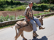 Man riding a donkey through Dol, Bra? island, Croatia .<br /> <br /> Visit our CROATIA HISTORIC SITES PHOTO COLLECTIONS for more photos to download or buy as wall art prints https://funkystock.photoshelter.com/gallery-collection/Pictures-Images-of-Croatia-Photos-of-Croatian-Historic-Landmark-Sites/C0000cY_V8uDo_ls