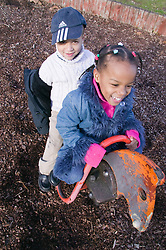 Little boy and girl having fun on a seesaw in the playground,