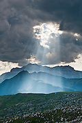 Crepuscular rays of sunlight break through clouds in the Dolomites, or Dolomiti, a part of the Southern Limestone Alps, in northern Italy, Europe. The view looks westwards from a trail west of Gasthaus Passo di Giau. The Dolomites are honored as a natural World Heritage Site (2009) by UNESCO.