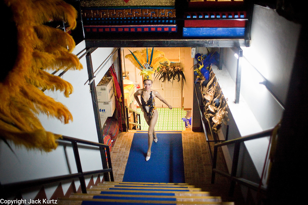 "Oct. 7, 2009 -- BANGKOK, THAILAND:  ""Ladyboys"" at the Mambo Cabaret in Bangkok, Thailand, run up the stairs to the stage at the opening of the show. The performers at the Mambo Cabaret in Bangkok, Thailand are all ""Ladyboys,"" or kathoeys in Thai. Recognized as a third gender, between male and female, they are born biologically male but live their lives as women. Many kathoey realize they are third gender in their early teens, some only as old 12 or 13. Kathoeys frequently undergo gender reassignment surgery to become women. Being a kathoey in Thailand does not carry the same negative connotation that being a transgendered person in the West does. A number of prominent Thai entertainers are kathoeys. Photo by Jack Kurtz / ZUMA Press"