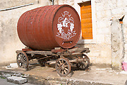 An old wooden cart with a big barrel for transporting wine used as a promotional sign outside the winery. Toreta Vinarija Winery in Smokvica village on Korcula island. Vinarija Toreta Winery, Smokvica town. Vinarija Toreta Winery, Smokvica town. Peljesac peninsula. Dalmatian Coast, Croatia, Europe.