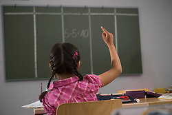 Schoolgirl in front of blackboard with raised hand in classroom, Munich, Bavaria, Germany