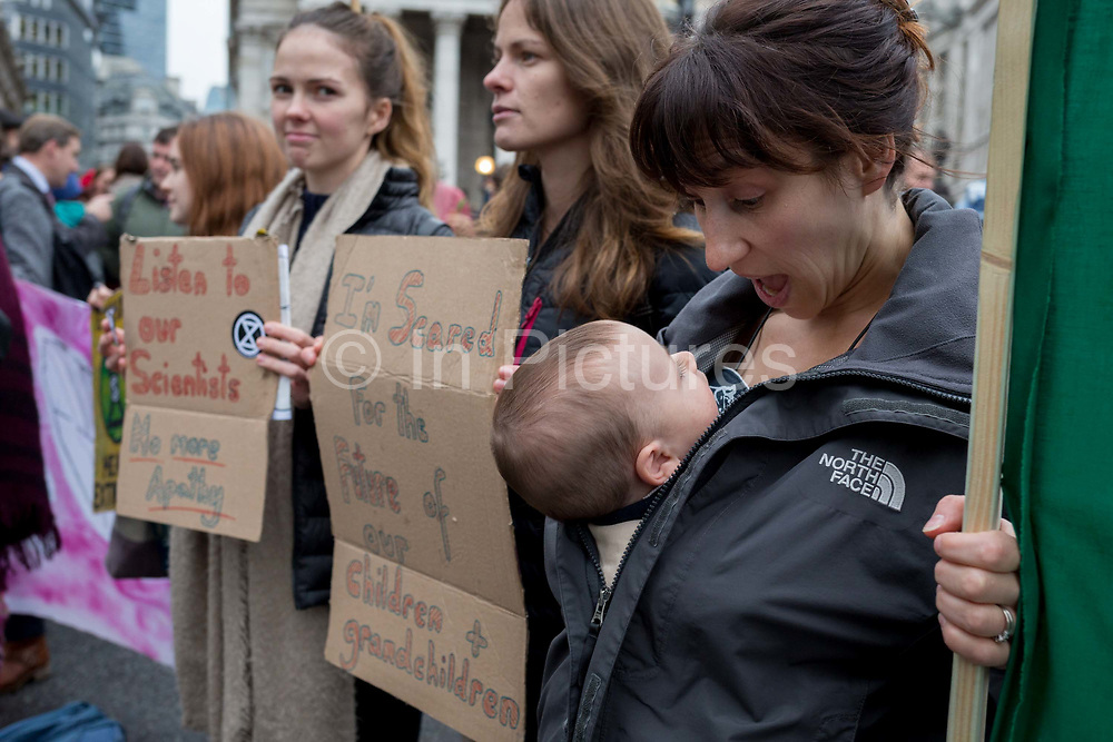 A mother and child environmental activists protest about Climate Change during the blockade at the junction at Bank in the heart of the capitals financial district, the City of London aka the Square Mile, on the seventh day of a two-week prolonged worldwide protest by members of Extinction Rebellion, on 14th October 2019, in London, England.
