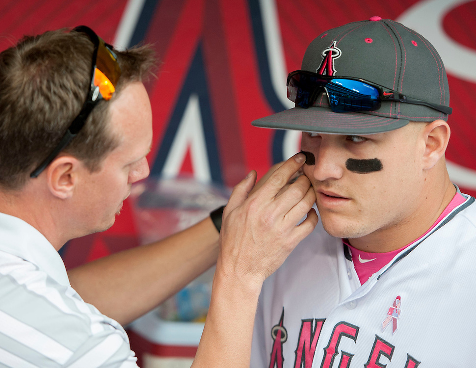 Mike Trout gets some help with his eye black from trainer Adam Nevala before the Angels game against Tampa Bay Sunday at Angel Stadium.<br /> <br /> ///ADDITIONAL INFO:   <br /> <br /> angels.0509.kjs  ---  Photo by KEVIN SULLIVAN / Orange County Register  --  5/8/16<br /> <br /> The Los Angeles Angels take on the Tampa Bay Rays at Angel Stadium Sunday.<br /> <br />  5/8/16