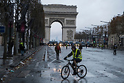 December, 8th, 2018 - Paris, Ile-de-France, France: Demonstrator with bicycle, Arc de Triomphe behind, on Champs Elysees. The French 'Gilets Jaunes' demonstrate a fourth day. Their movement was born against French President Macron's high fuel increases. They have been joined en mass by students and trade unionists unhappy with Macron's policies. Nigel Dickinson
