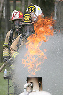 Joe Holmes, from the Pine Township Volunteer Fire Department, leads a line of firefighters including Chris Holmes, also Pine Township, and Ken Taggart, Slippery Rock, while putting out a fire on a propane tank at a training session at the Hermitage Volunteer Fire Department.