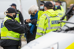 West Hyde, UK. 9th September, 2020. Hertfordshire Police officers arrest an anti-HS2 activist who blocked one of several entrances to the Chiltern Tunnel South Portal site for the HS2 high-speed rail link for the entire day. The protest action, at the site from which HS2 Ltd intends to drill a 10-mile tunnel through the Chilterns, was intended to remind Prime Minister Boris Johnson that he committed to remove deforestation from supply chains and to provide legal protection for 30% of UK land for biodiversity by 2030 at the first UN Summit on Biodiversity on 30th September.