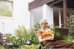 Young woman using laptop in the domestic garden, Munich, Bavaria, Germany