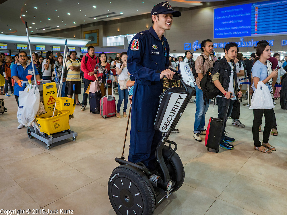 """24 DECEMBER 2015 - BANGKOK, THAILAND:  A member of a Thai police bomb squad uses a Segway to patrol the new domestic terminal at Don Muang (also spelled Don Mueang) International Airport. The new terminal had its """"soft"""" opening Dec. 24. Don Muang is the airport used by low cost airlines serving Bangkok and is now the largest airport in the world for low cost carriers. In 2014, more than 21million passengers used Don Muang. Don Muang International Airport is the oldest airport in Asia and one of the oldest airports in the world. It started functioning as an airfield in 1914.    PHOTO BY JACK KURTZ"""