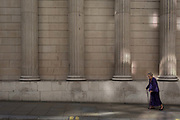 An elderly lady walks slowly beneath the pillars and columns of the Bank of England in Bartholomew Lane, in the City of London, the capitals financial district aka the Square Mile, on 15th May 2018, in London, UK.