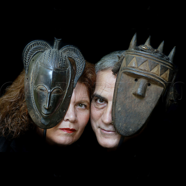 Art collectors Vilma and Behrooz Garabaghi with a Yaure mask from the Ivory Coast on the left and a Toma Mask from Liberia on the right.