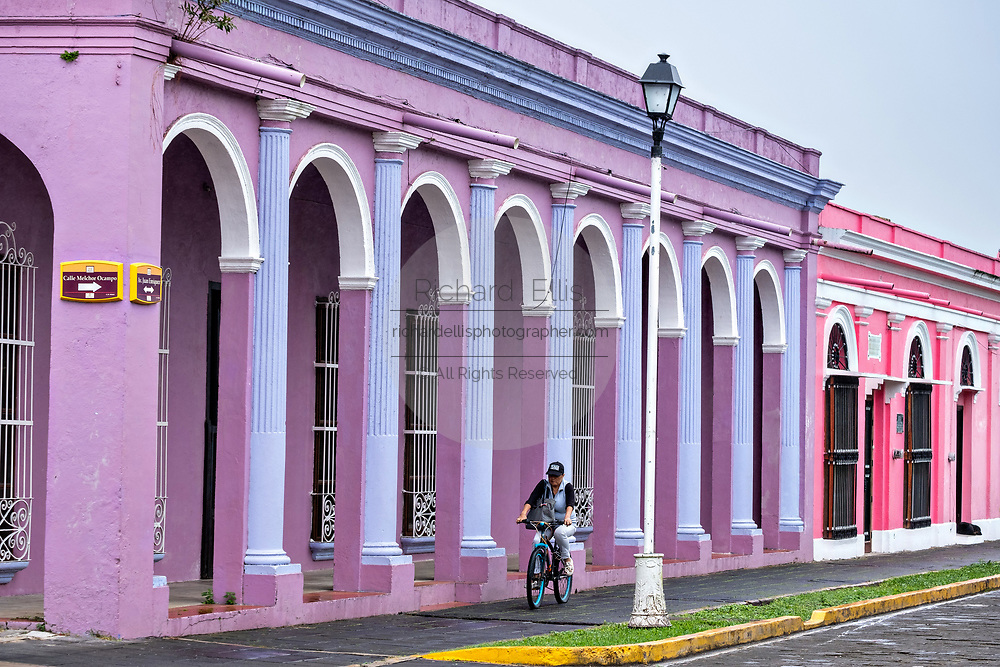 A bicyclist rides past the colorful colonnade style buildings in Tlacotalpan, Veracruz, Mexico. The tiny town is painted a riot of colors and features well preserved colonial Caribbean architectural style dating from the mid-16th-century.