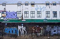 Grafiti on the backside of a building by Frakkastigur in 101 Reykjavík. Residents cooling their food by hanging it in plastic bags from a window. Bakhús með veggjakroti við Frakkastíg. Matvæli kæld með því að hengja plastpoka út um glugga á efstu hæð.