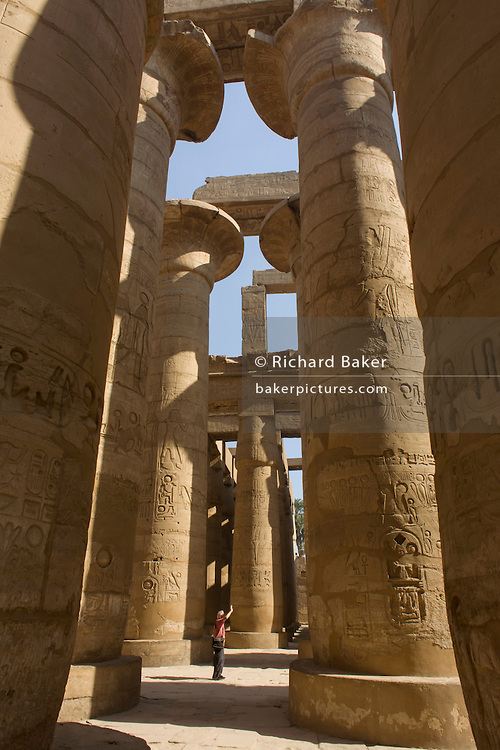 The tall columns in the Hypostyle hall at the Temple of Amun at Karnak, Luxor, Nile Valley, Egypt. The Karnak Temple Complex is the largest religious building ever made, covering about 200 acres. It comprises a vast mix of decayed temples, chapels, pylons, and other buildings built over 2,000 years and dedicated to the Theban triad of Amun, Mut, and Khonsu. The Hypostyle hall, at 54,000 square feet (16,459 meters) and featuring 134 columns, is still the largest room of any religious building in the world.
