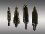 Black obsidian arrow heads. Catalhoyuk Collections. Museum of Anatolian Civilisations, Ankara. Against a grey background .<br /> <br /> If you prefer you can also buy from our ALAMY PHOTO LIBRARY  Collection visit : https://www.alamy.com/portfolio/paul-williams-funkystock/prehistoric-neolithic-art.html - Type Catalhoyuk into the LOWER SEARCH WITHIN GALLERY box. Refine search by adding background colour, place, museum etc.<br /> <br /> Visit our PREHISTORIC PLACES PHOTO COLLECTIONS for more  photos to download or buy as prints https://funkystock.photoshelter.com/gallery-collection/Prehistoric-Neolithic-Sites-Art-Artefacts-Pictures-Photos/C0000tfxw63zrUT4