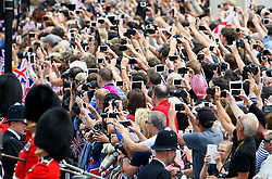 © Licensed to London News Pictures. 11/06/2016. London, UK. Members of the public use mobile phones and cameras to film Queen Elizabeth II during Trooping The Colour ceremony in London,  part of a weekend of celebration to mark the 90th birthday of Queen Elizabeth II,  Britain's longest reigning monarch. Photo credit: Ben Cawthra/LNP