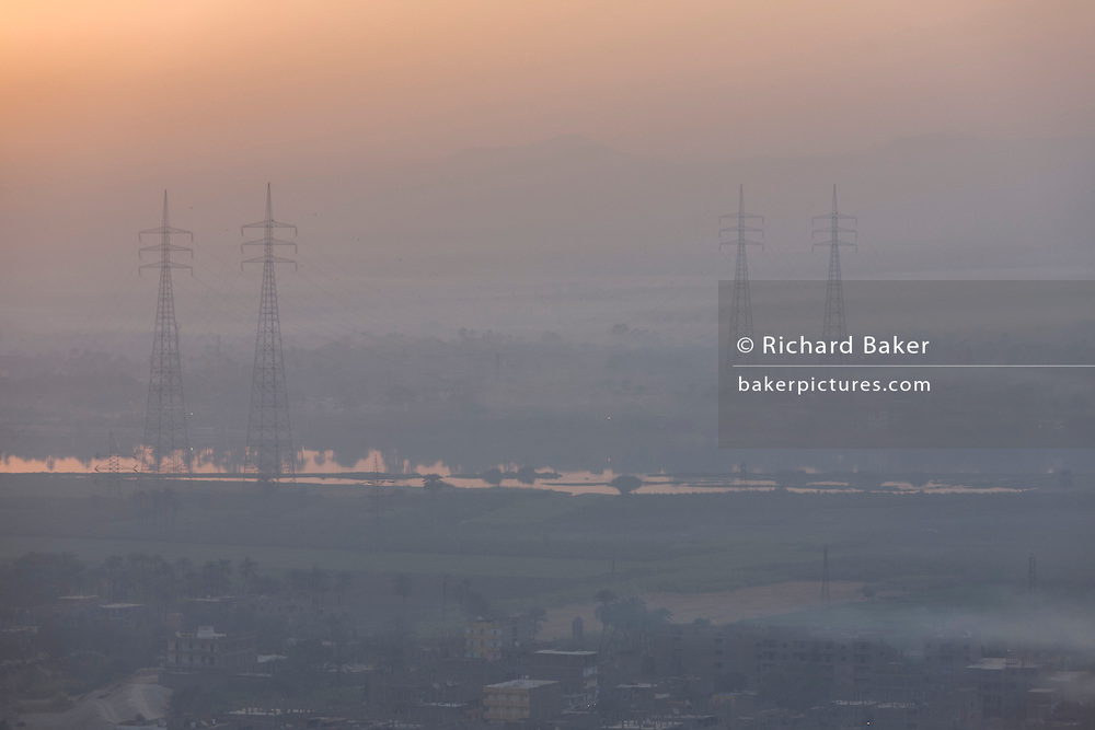 Looking east from the West Bank bank of the river Nile, of a rising sun with electricity power pylons above the city of modern Luxor, Nile Valley, Egypt.