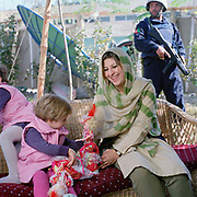 "Hassina Syed,  business woman, with her two daughters Sana (age 3)and Hirah(2), photographed at her home and business the Gandamack Lodge Hotel.  She also rents armoured cars, runs a farming business, a travel agency and a bedding shop. She is married to Peter Jouvenal an ex soldier, journalist and westerner who has lived in Afghanistan for twenty years.<br /> <br /> She experienced first hand, how terrifying the Taliban could be. She says: <br /> <br /> 'I opened up the Chadri (mesh front of the burkha) to see a tea-cup and suddenly from the back, a Taliban soldier came with a big stick, shouting at me. If you get beaten by a Taliban, you could die. <br /> ""I made myself look as old and bad as possible because if  they ( the Taliban) saw you looking even a bit beautiful, they could come to your house and take you as one of their wives""<br /> <br /> ""For me having money is dangerous, kidnapping is a big problem. A friend's uncle was kidnapped; they wanted $150 000, He was so mad he said, 'I am not paying that he is an old man!'  Eventually they dropped the price and said OK, just cover our fuel and the bribe for the police (30 000 dollars)."""