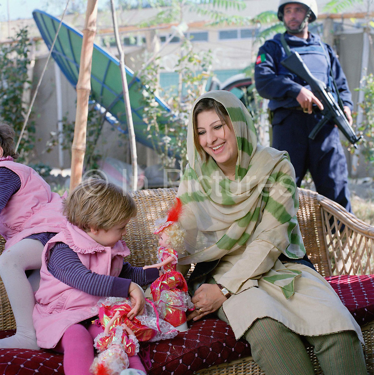 """Hassina Syed,  business woman, with her two daughters Sana (age 3)and Hirah(2), photographed at her home and business the Gandamack Lodge Hotel.  She also rents armoured cars, runs a farming business, a travel agency and a bedding shop. She is married to Peter Jouvenal an ex soldier, journalist and westerner who has lived in Afghanistan for twenty years.<br /> <br /> She experienced first hand, how terrifying the Taliban could be. She says: <br /> <br /> 'I opened up the Chadri (mesh front of the burkha) to see a tea-cup and suddenly from the back, a Taliban soldier came with a big stick, shouting at me. If you get beaten by a Taliban, you could die. <br /> """"I made myself look as old and bad as possible because if  they ( the Taliban) saw you looking even a bit beautiful, they could come to your house and take you as one of their wives""""<br /> <br /> """"For me having money is dangerous, kidnapping is a big problem. A friend's uncle was kidnapped; they wanted $150 000, He was so mad he said, 'I am not paying that he is an old man!'  Eventually they dropped the price and said OK, just cover our fuel and the bribe for the police (30 000 dollars)."""""""