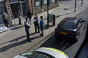 Seen from a London bus, two Met Police officers question a car driver in the borough of Southwark, on 19th April, in the City of London, England.