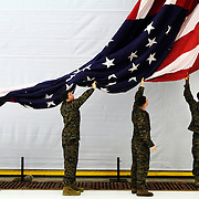 Cpl. Jose Valenzuela, Seaman Justin Corbin,  Cpl. Jacob Fantin, and Cpl.  Shantonio Graham, keep a large American flag that weas used during the change of command and retirement ceremony at the Marine Corps Air Station Beaufort from touching the ground on February 13, 2014.  Colonel Brian C. Murtha  will relinquish command of the Air Station to Col. Peter D. Buck, who most recently served as the chief of staff at 2nd Marine Aircraft Wing in Cherry Point, N.C.