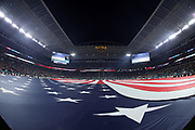 The American flag is draped over the field during the singing of the National Anthem in this wide angle general view photograph taken with a fisheye lens before the Miami Dolphins 2017 NFL week 14 regular season football game against the New England Patriots, Monday, Dec. 11, 2017 in Miami Gardens, Fla. The Dolphins won the game 27-20. (©Paul Anthony Spinelli)
