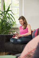 Young woman using digital tablet in living room and smiling, Munich, Bavaria, Germany