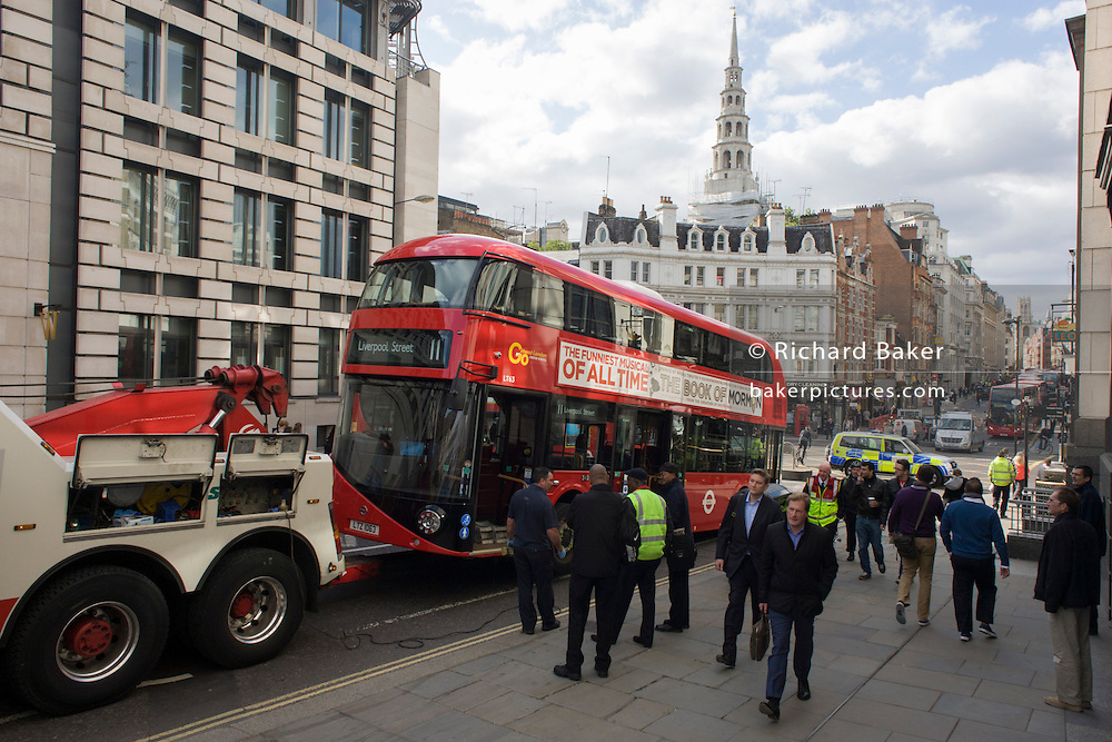A new model of Routemaster bus has broken down and disrupts traffic in a City of London street. The New Bus for London, sometimes referred to as NB4L, and colloquially as the New Routemaster or Borismaster (after the Mayor of London who drove their introduction) is a 21st-century replacement of the iconic AEC Routemaster as a bus built specifically for use in London. Designed by Heatherwick Studio, it is built by Wrightbus, and features the 'hop-on hop-off' rear open platform of the original Routemaster, but meets the requirements for modern buses to be fully accessible. The first bus entered service on 27 February 2012. The cost of each bus is £354,500.