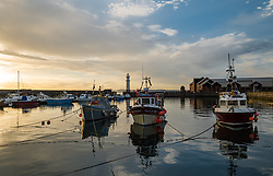 Edinburgh, Scotland, UK, 16th June 2021. Sunset at Newhaven Harbour: People were treated to a colourful sunset this evening with calm water reflecting the colours of the sky.<br /> Sally Anderson | EdinburghElitemedia.co.uk