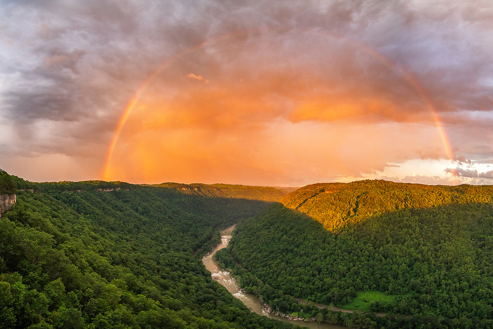 A rainbow appears to span the length of the canyon at the end of a storm with the setting sun casting an orange glow over the New River Gorge in West Virginia.