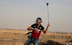 May 24, 2019 - Gaza, khan younis, Palestine - A Palestinian demonstrator seen throwing stones using a  slingshot during the clashes..Palestinians clashed with Israeli forces during a major demonstration on the Gaza border, calling for an end to the Israeli siege on Gaza and the right to return to their homes at the border fence between Israel and Gaza in the southern Gaza Strip. (Credit Image: © Yousef Masoud/SOPA Images via ZUMA Wire)