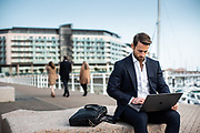 Businessman sat on a wall working on his laptop at the Elizabeth Marina with views beyond of boats and the Castle Quay Apartments, Jersey, CI