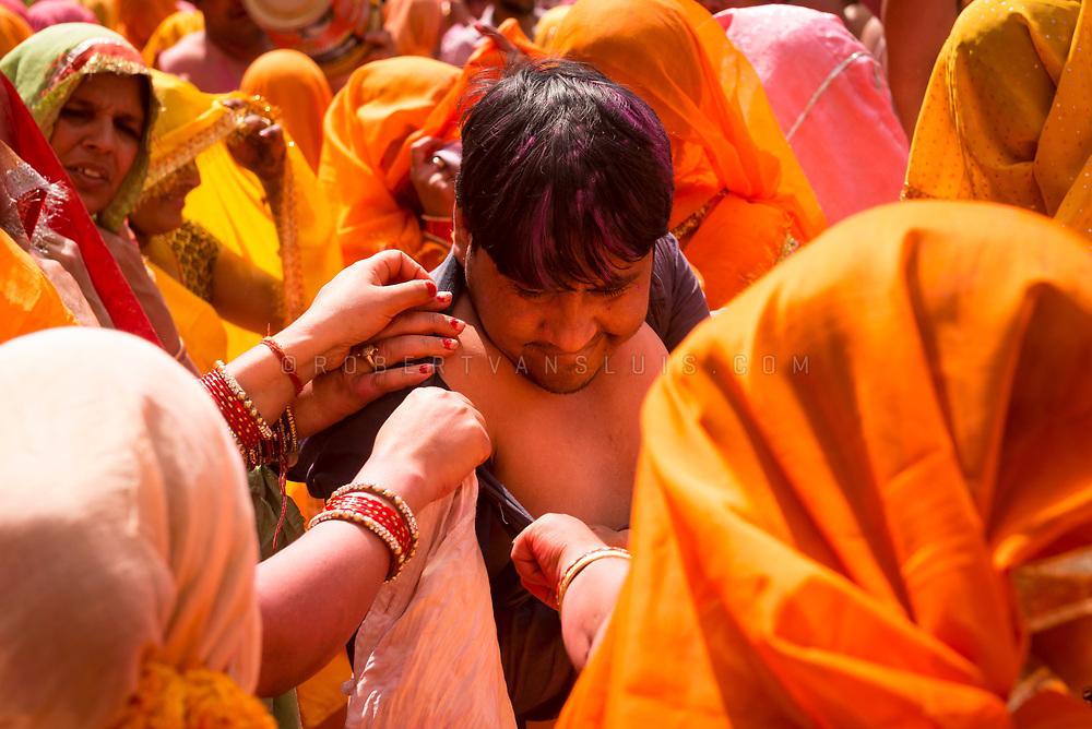 Women strip a man at the Huranga festival, Dauji temple, Baldeo, India. Photo © robertvansluis.com