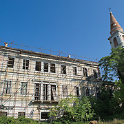 """VENICE, ITALY - AUGUST 27:  External view of the abandoned """"Stazione Sanitaria di Poveglia"""" (Hospital of Poveglia) with the San Vitale belfry on August 27, 2011 in Venice, Italy. The island of Poveglia, with its ruined hospital and plague burial grounds, is said to be the most haunted location in the world. Though it is a multi-million dollar piece of real estate it lies deserted and off limits to the public. Its dark, forbidding shores are only minutes away from the glamour of the Venice Film Festival on the Lido. ...To discuss licensing our 4000 word photo documentary of the island, email robin@robinsaikia.com. ..British author Robin Saikia visited the site with Italian photographer Marco Secchi. Marco captured the sinister atmosphere of the island. Robin describes the terrifying apparitions and the stories behind them."""