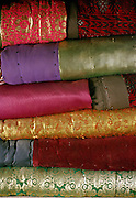 Colorful and golden Afghan Kyrgyz blankets stacked up. In Winter, Afghan Kyrgy use 4 or 5 of these blankets to keep warm..Campment of Ortobil (Sufi), all the way at the end of the Little Pamir, near the Tajik/China border. .Winter expedition through the Wakhan Corridor and into the Afghan Pamir mountains, to document the life of the Afghan Kyrgyz tribe. January/February 2008. Afghanistan