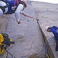 BAFFIN ISLAND, Canada. John Catto films Mark Synnott & Jared Ogdon (MR) high up 4000' granite face on Great Sail Peak.
