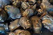 Spare buddha heads of bronze casts are left lying around,after failing quality control, Phraruangsamai Buddha Factory.