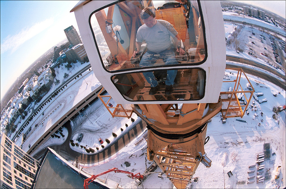 A tower crane operator sits 240 feet above the ground during the winter in Edina, Minnesota.