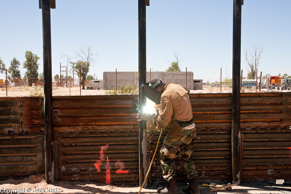 12 JUNE 2006 - SAN LUIS, AZ: Sgt. David Cowley, a welder with the Utah National Guard, welds a joint in a fence near San Luis, AZ. San Luis, Mexico is on the other side of the fence. Fifty five members of the 116th Engineer Company, Combat Support Engineers, of the Utah Army National Guard are in San Luis, AZ, to build a fence and improve roads east of the San Luis Port of Entry on the US/Mexico border. The unit is the first of an estimated 6,000 US military personnel, almost all of them Army National Guard, who will be dispatched to the US/Mexico border by President Bush to help control immigration on the border. The Guardsmen will primarily build roads and fence and staff surveillance centers. They will not be engaged in first line law enforcement work.  Photo by Jack Kurtz
