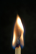 single match that is burning against a black background