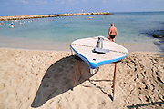 Israel, Haifa, Israelis go to the Beach on a warm, sunny day. A Hasakeh or flatboard boat used by the lifeguards in case of emergency .