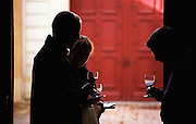 Dark Silhouettes of three people two men and a woman tasting wines glasses and note books notebooks in hand in a doorway against a background of a red door, at Chateau Carbonnieux, Graves, Pessac-Leognan, Bordeaux Gironde Aquitaine France Europe
