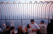 With the New York skyline shrouded in smog, a young Asian couple embrace on the open-air deck of the Empire State Building in Manhattan, on 31st July 1998, in New York, USA.