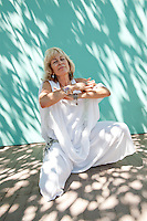 """Middle aged woman in white in a mediatation moment.<br /> :::<br /> """"Abundance is not something we acquire. It is something we tune into.""""<br /> -Wayne Dyer"""